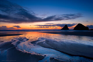 Dramatic sunset colors divide the ocean from the sky at Heceta Beach, Oregon.