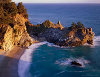 McWay Falls cascades onto golden sand lit by sunset light in the pristine cove at Julia Pfeiffer State Park in the Big Sur section of California coast.