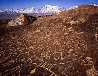 Native American petroglyphs, ancient writing full of culture and beauty, beneath the backdrop of the snow-capped Eastern Sierra Nevada range.