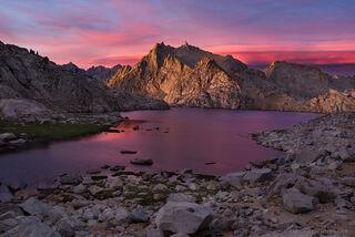Pink sunset light illuminates Colombine Lake and the Sierra Nevada range in Sequoia National Park, California.