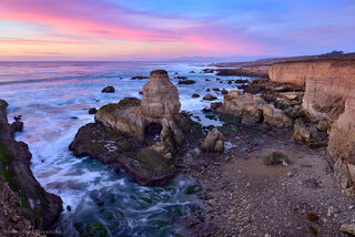 Evening sunset light paints the ocean and sky pink on the rocky cliffs of Montana de Oro State Park on the beautiful California coast.