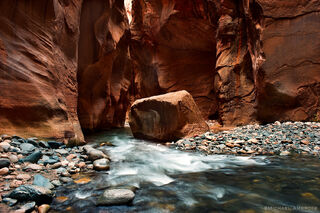 A river runs through a deep slot canyon in the narrows section of Zion National Park.