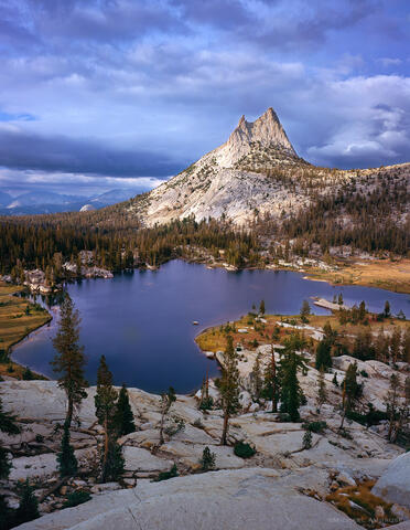 Cathedral Peak is illuminated in stormy  light above stormy Upper Cathedral Lake located in the Tuolumne Meadows section of Yosemite National Park.