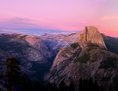 In Yosemite, half dome glows pink in alpenglow sunset light as seen from Glacier Point.