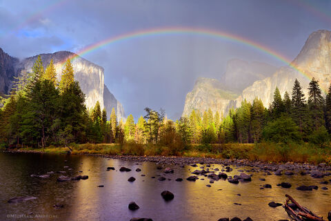 The Gates of the Valley view of Yosemite Valley is draped with a dramatic rainbow and mist, in Yosemite National Park.