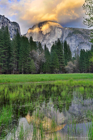 Half dome reflects in the flooded Ahwahnee Meadow as a storm breaks over Yosemite Valley.