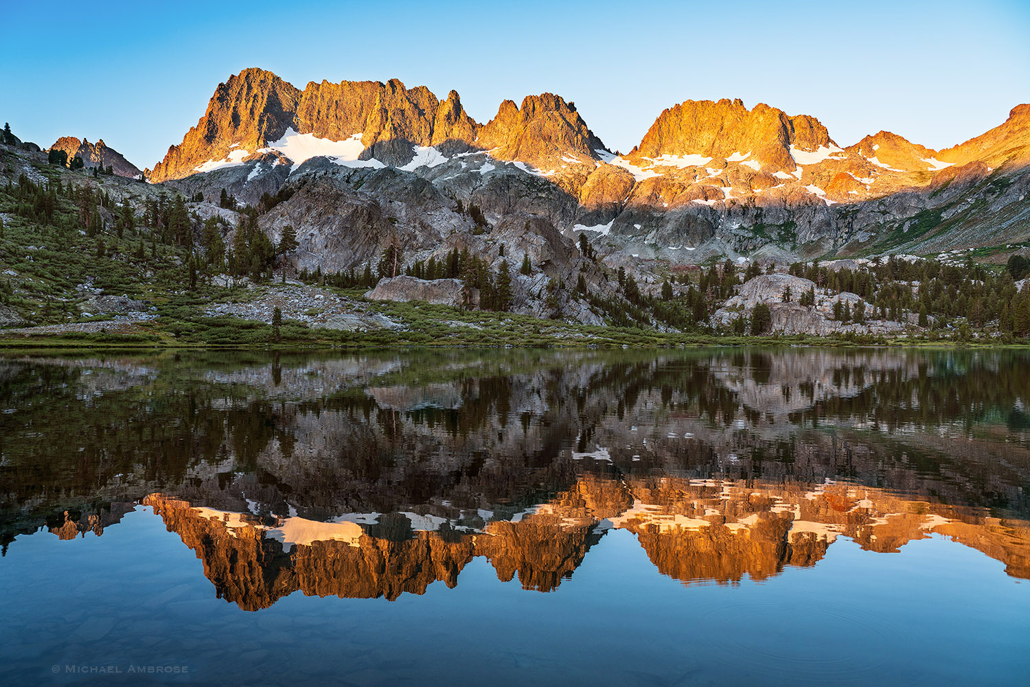 The Minarets reflect in Ediza lake as a perfect backcountry view in the Ansel Adams Wilderness and Mammoth Lakes Sierra.