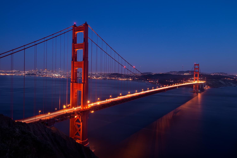 Nighttime approaches and illuminates the famous Golden Gates Bridge, connecting San Francisco to Marin Headlands, California.