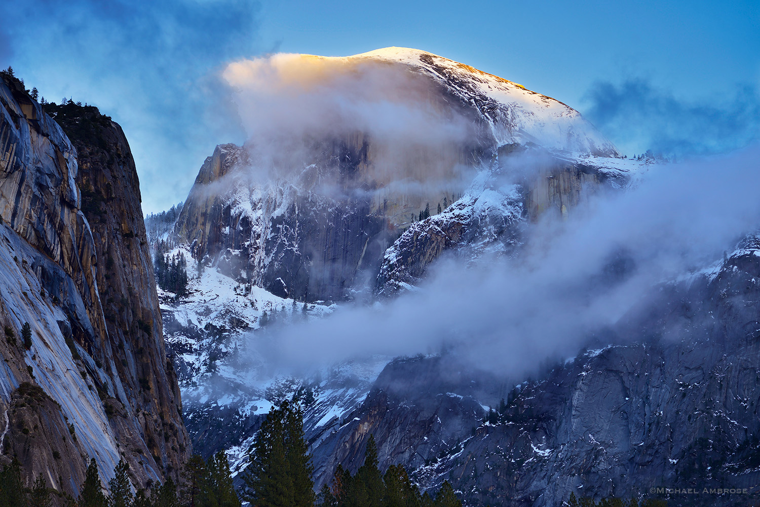 Half Dome in Yosemite Valley is shrouded in winter clouds and snow.