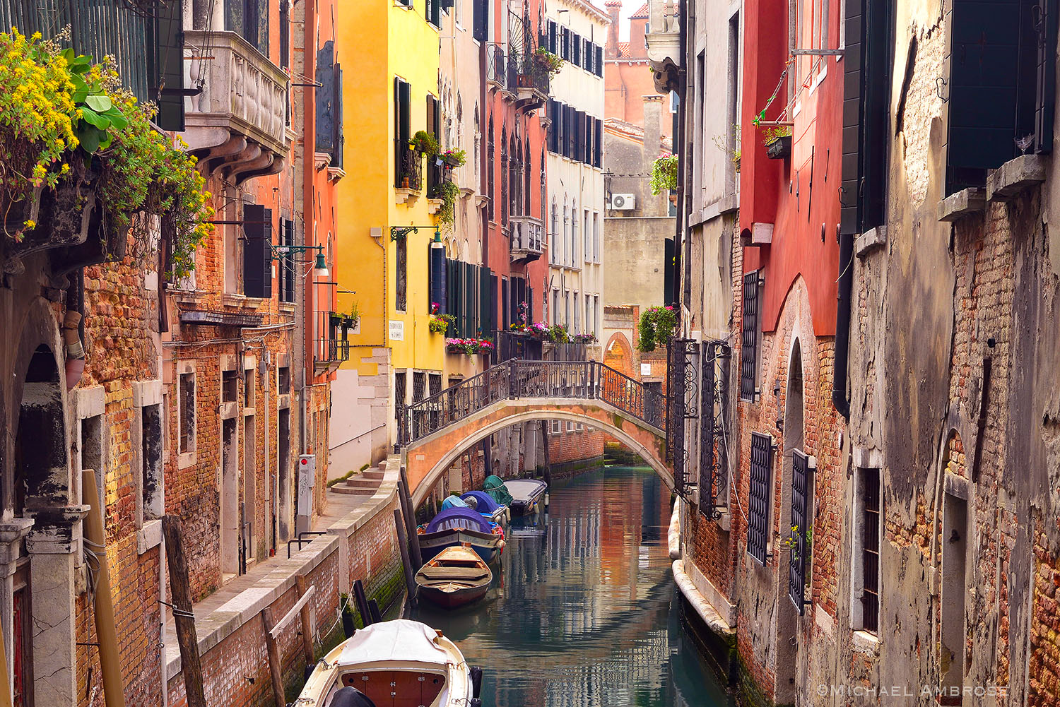 Beautifully weathered buildings and footbridges reflect in the brightly colored Venice canal.