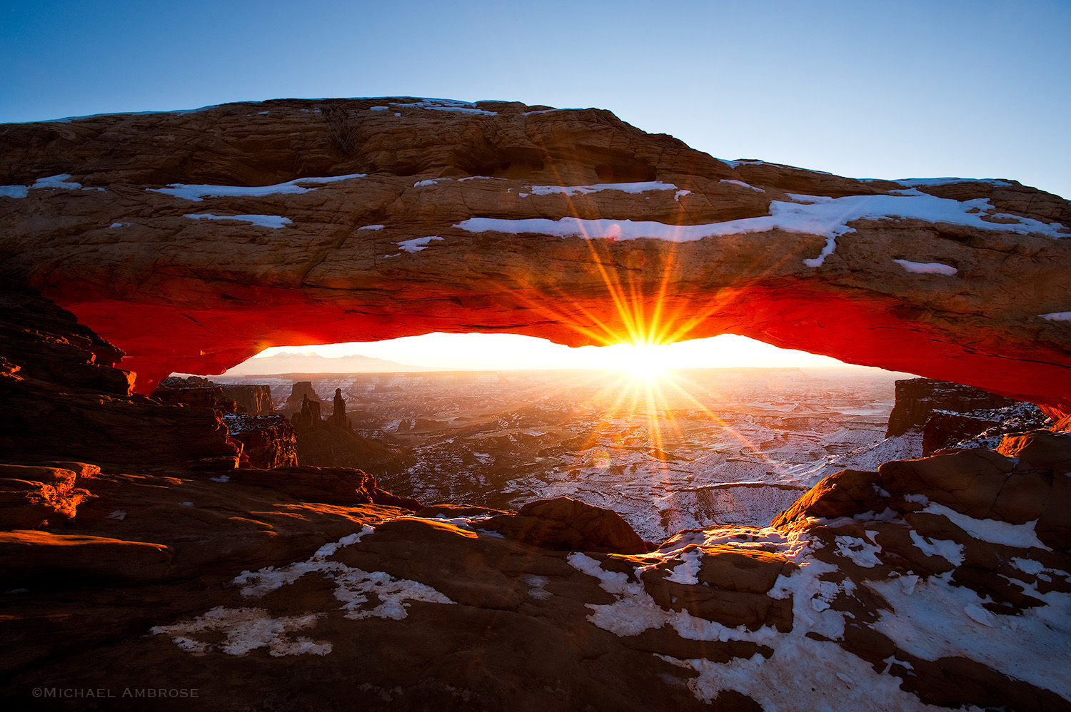 Mesa Arch, etched with snow,  glows with a starburst in Cayonlands National Park, in Utah.