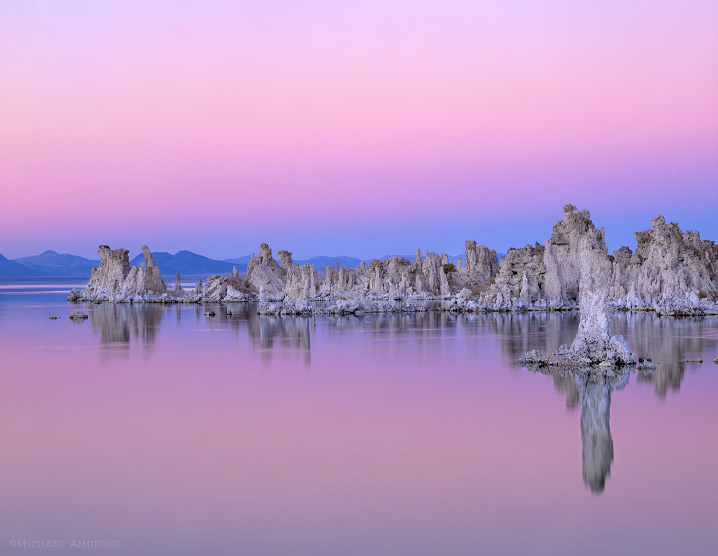 Tufa towers divide the eastern Sierra  pink sunset sky from Mono lake in Lee Vining, California.