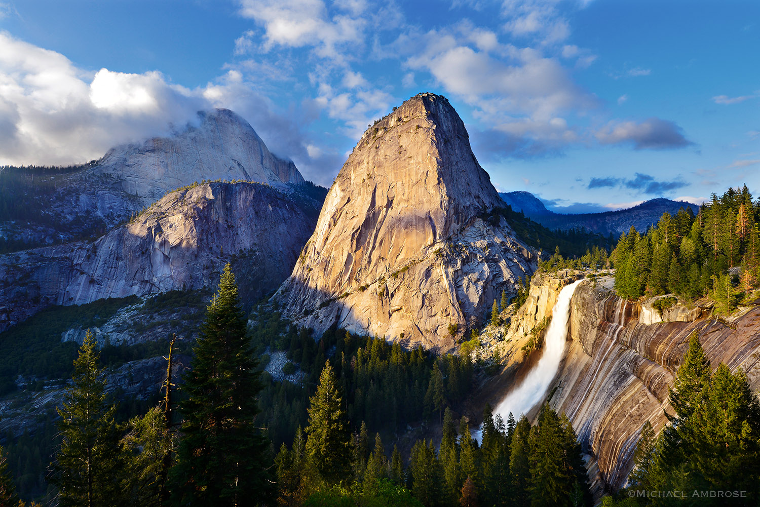 Springtime in Yosemite boasts a rushing water and glowing granite; Nevada fall, Liberty Cap, and Mt. Broderick bask in stormy light
