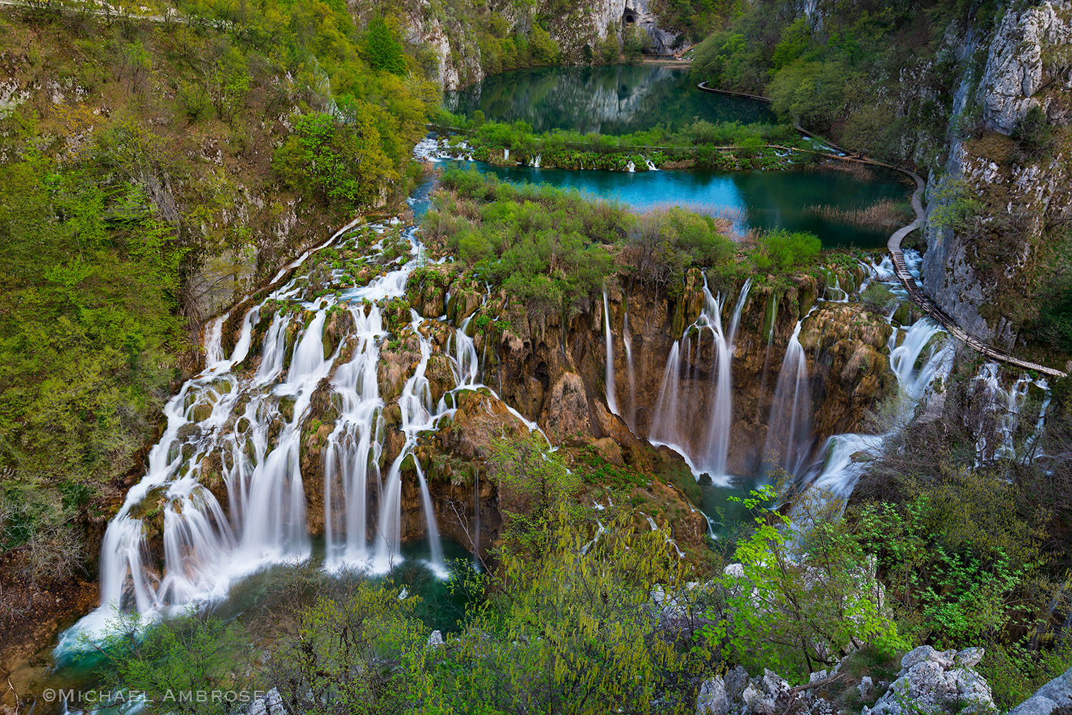 Lakes, waterfalls and cascades join and follow wooden paths hovering just above deep blue water in Plitvice National Park in Croatia.