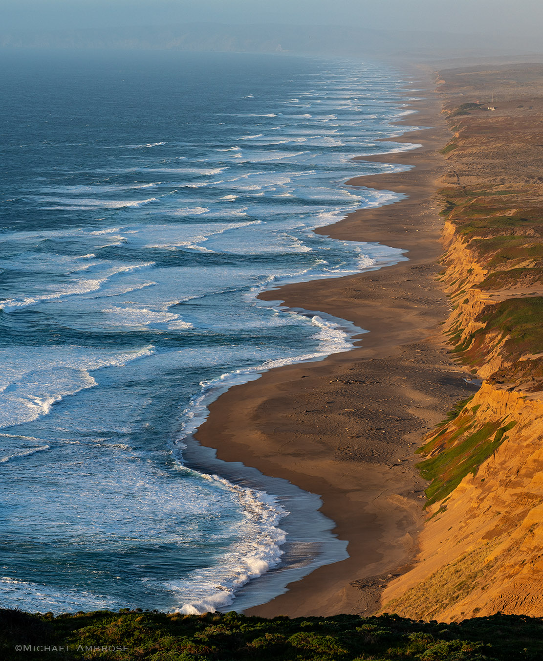Like lace adorning a collar, the layers of waves, sand, and cliffs glisten in the evening sun a Point Reyes National Seashore in California.